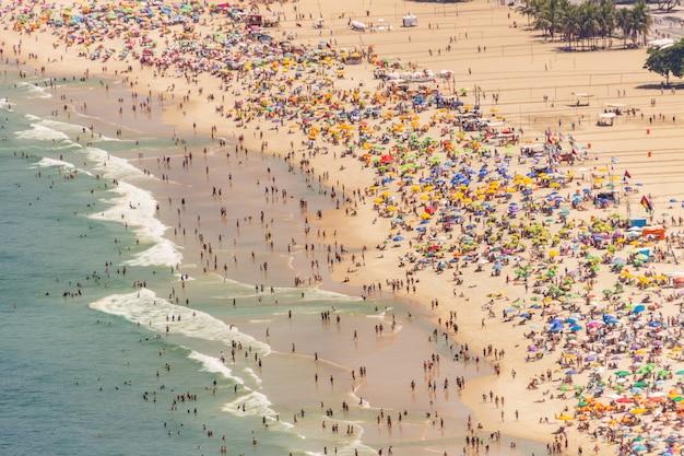 Praia de copacabana cheia em um típico domingo ensolarado no rio de janeiro.