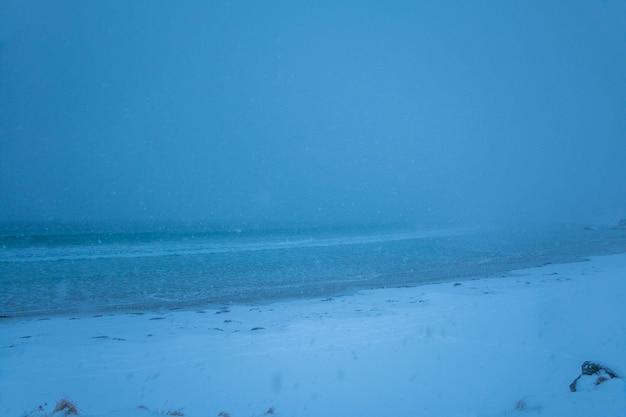 Praia de inverno. uma forte nevasca esconde o horizonte. visibilidade mínima