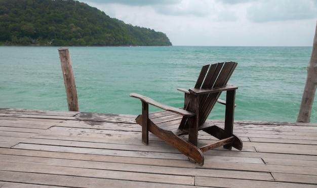 Praia de madeira do cais com a cadeira no fundo do mar.