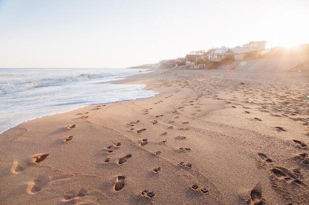 Praia de mar iluminada pelo sol. pegadas na areia