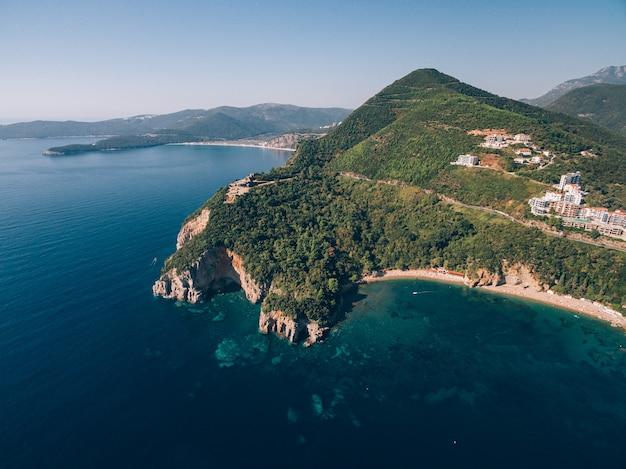 Praia de mogren perto da cidade velha de budva, em montenegro, o antigo forte de mogren na montanha rochosa