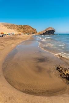 Praia de monsul no parque natural cabo de gata, formações de lava erodidas que a rodeiam, areia fina e água cristalina