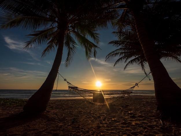 Praia de phuket, tailândia. silhueta de rede e palmeiras na praia tropical ao pôr do sol. rede em uma palmeira e o brilho do sol perto da areia da costa do mar oceano céu.