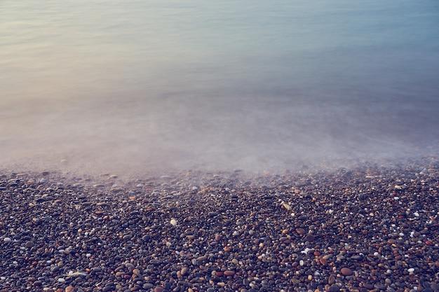 Praia de seixos em kolymbari em creta ao pôr do sol. copie o espaço.