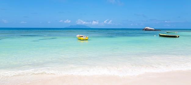 Praia de verão com céu ensolarado e fundo de água azul