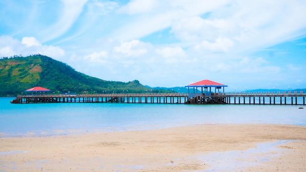 Praia de verão e a ponte de barco que se estende para o mar perto da ilha