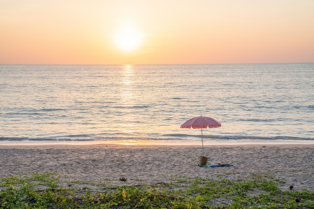 Praia de verão e guarda-chuva vermelho para o conceito de férias