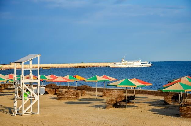 Praia de verão perto do mar - camas de cavalete, guarda-sóis para sombra, torre que salva vidas