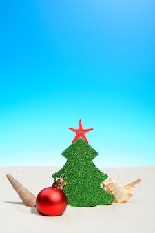 Praia de verão tropical natal com uma árvore de natal, bugigangas e conchas na areia dourada e copie o espaço para sua saudação no céu azul