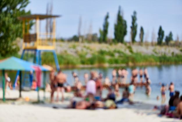 Praia desfocada com uma multidão em um dia ensolarado de calor.