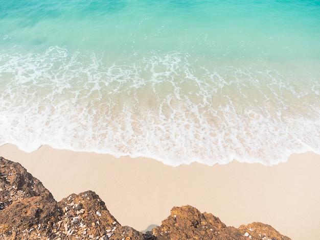 Praia do mar azul com ondas macias brancas e pedra para viagens ou férias de verão.