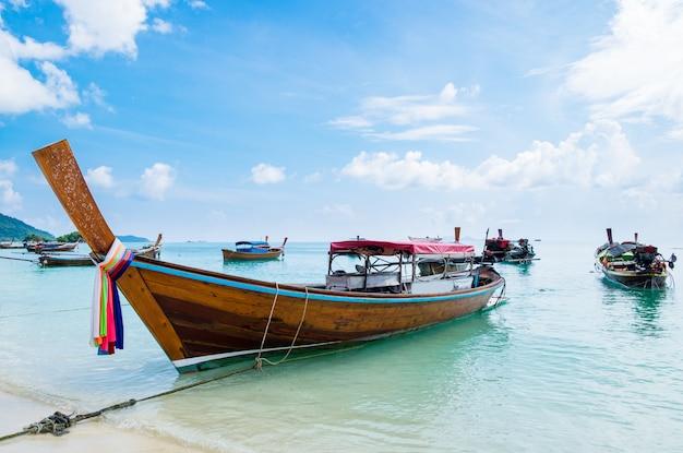 Praia do mar com costa de âncora de barco de cauda longa de grupo