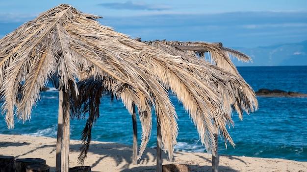 Praia do mar egeu com guarda-sóis feitos de ramos de palmeira na grécia