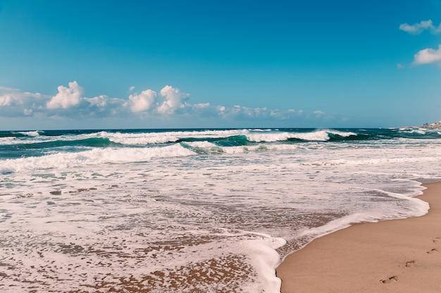 Praia do oceano com pegadas na areia amarela, céu azul, nuvens brancas, ondas turquesas