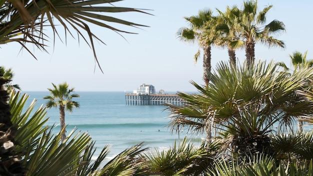 Praia do oceano pacífico, palmeiras verdes e cais. dia de sol, resort tropical à beira-mar. ponto de vista em oceanside, perto de los angeles califórnia, eua. estética da costa do mar de verão, vista do mar e céu azul.