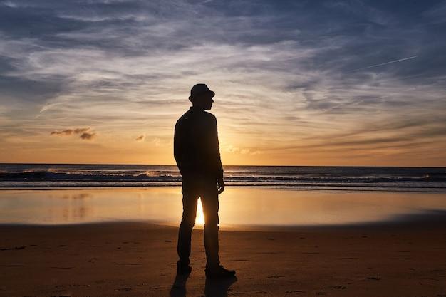 Praia do pôr do sol do oceano da espanha, andaluzia. ondas do oceano atlântico, fundo do céu mágico brilhante do pôr do sol