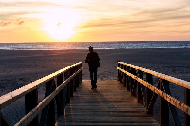 Praia do pôr do sol do oceano da espanha, andaluzia. ondas do oceano atlântico, fundo do céu mágico brilhante do pôr do sol Foto Premium