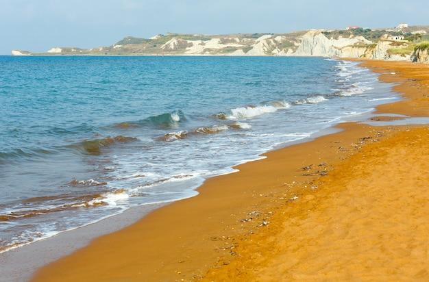 Praia do xi com areia laranja e falésias brancas. vista de manhã na grécia, kefalonia. mar jônico.