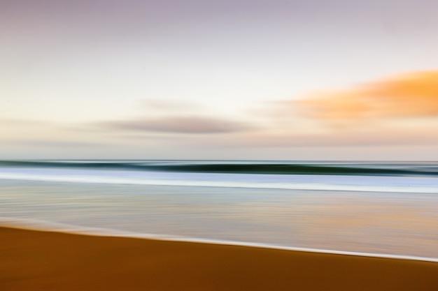 Praia durante o pôr do sol com efeito de movimento