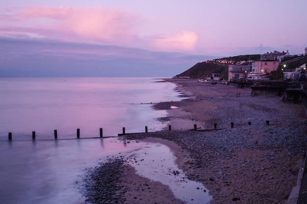 Praia durante o pôr do sol em bognor regis, west sussex, reino unido