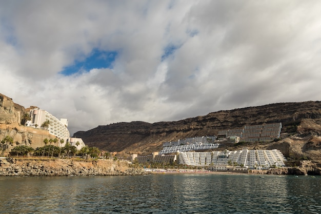 Praia e hotéis vistos do mar, céu nublado