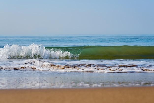 Praia em um pôr do sol com reflexo na areia molhada e ondas com espuma