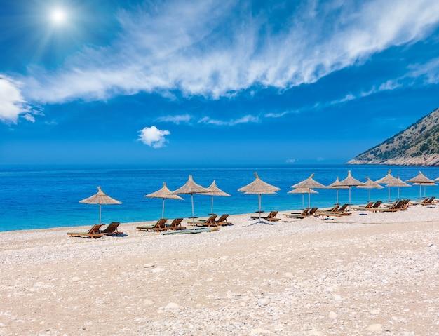 Praia ensolarada de verão com água azul-marinho e nuvens no céu, espreguiçadeiras e guarda-sóis de palha (albânia).