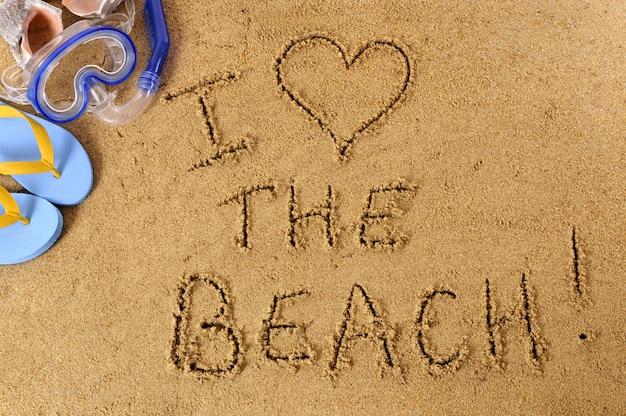 Praia escrevendo com máscara de mergulho, conchas e chinelos