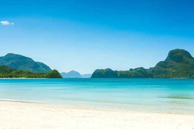 Praia exótica fabulosa com areia branca e palmeiras altas, filipinas, el nido