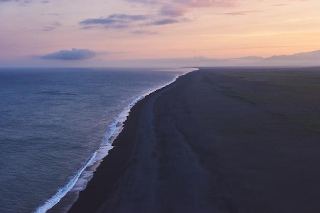 Praia fantástica no sul da islândia, lava de areia preta. o pôr do sol pitoresco com dramáticas nuvens cumulus