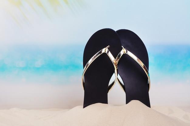 Praia flip-flops na bela praia de areia perto do oceano. espaço da cópia