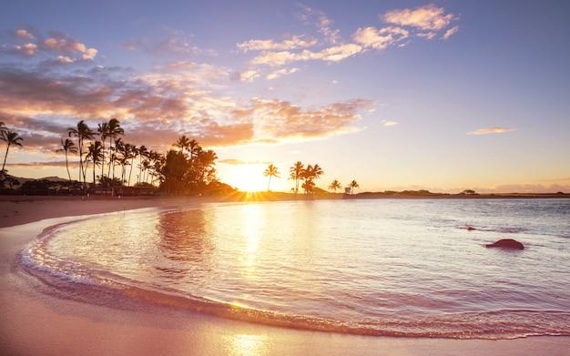 Praia havaiana incrível ao pôr do sol fantástico.