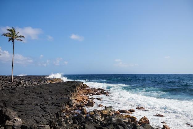 Praia havaiana incrível. onda no oceano e na costa de lava vulcânica