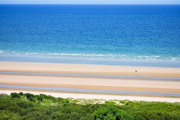 Praia longa e calma com céu azul nublado.