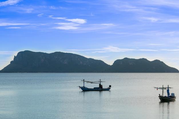 Praia, mar durante a estação de verão no nascer do sol da manhã com o barco de pesca pequeno.