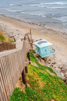 Praia na praia em los angeles, torres azuis de salva-vidas ao pôr do sol na costa da califórnia