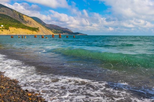Praia pedregosa da costa do mar negro na vila de bolshoy utrish cheia de pessoas em um verão ensolarado