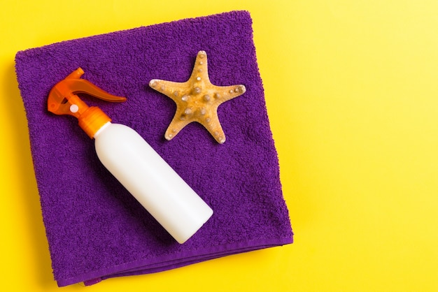 Praia plana leigos acessórios com espaço de cópia. toalha azul e branca violeta, conchas do mar, chapéu de sol staw e uma garrafa de protetor solar em fundo amarelo. conceito de férias de verão
