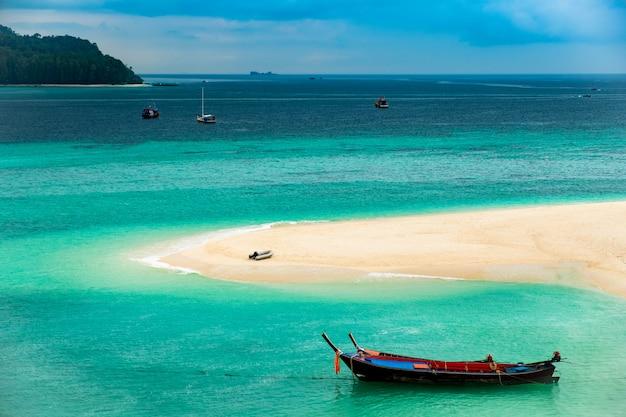 Praia que se estende para o mar olhando para ver a ilha e o céu azul