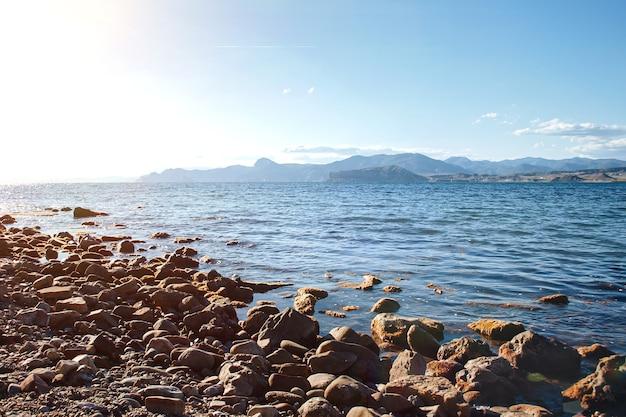 Praia rochosa com fundo de céu azul e montanhas