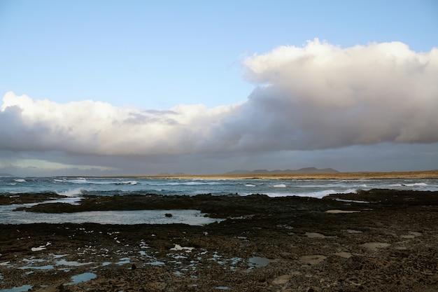 Praia rochosa e tempo nublado