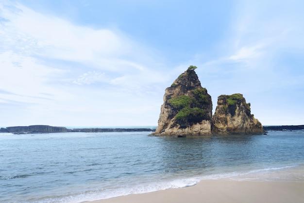 Praia rochosa tomada em dia ensolarado