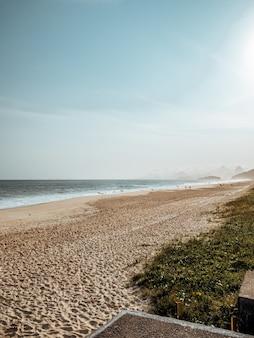 Praia rodeada de mar e grama sob o sol no rio de janeiro, brasil
