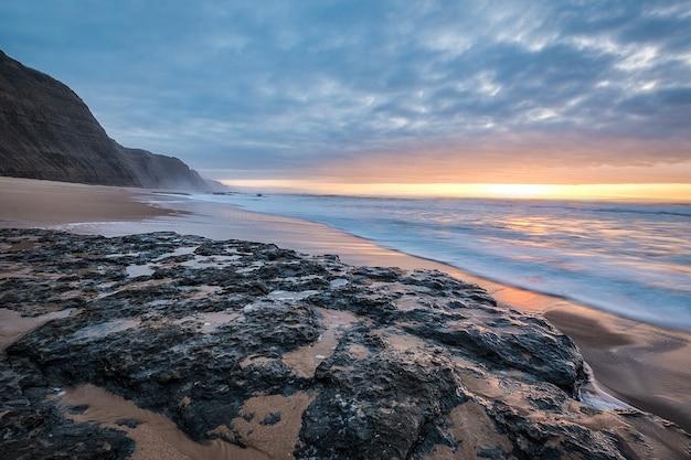 Praia rodeada de pedras e mar sob um céu nublado durante um lindo pôr do sol