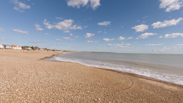 Praia rodeada pelo mar e edifícios sob o sol e céu azul durante o dia