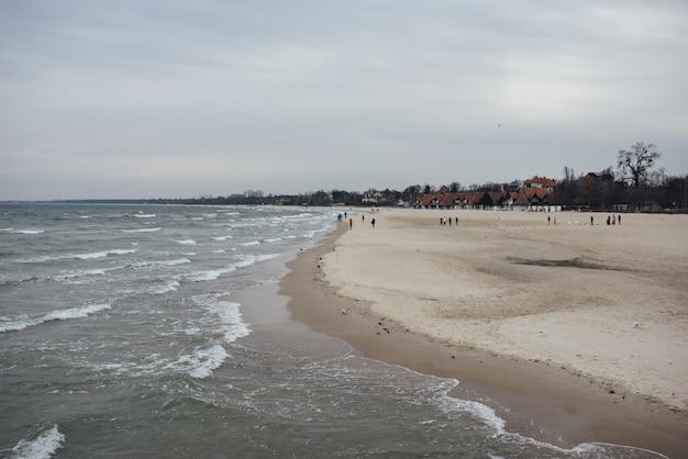 Praia rodeada pelo mar e edifícios sob um céu nublado durante o dia