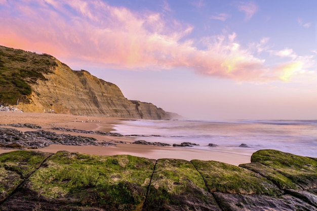 Praia rodeada pelo mar e falésias cobertas de musgos sob um céu nublado durante o pôr do sol