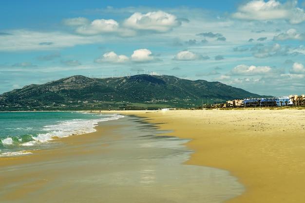 Praia rodeada pelo mar e montanhas sob o sol em tarifa, espanha