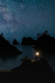 Praia secreta oregon à noite com estrelas e viajante em pé com a luz
