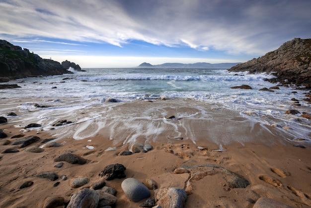 Praia selvagem com pedras e nuvens de areia